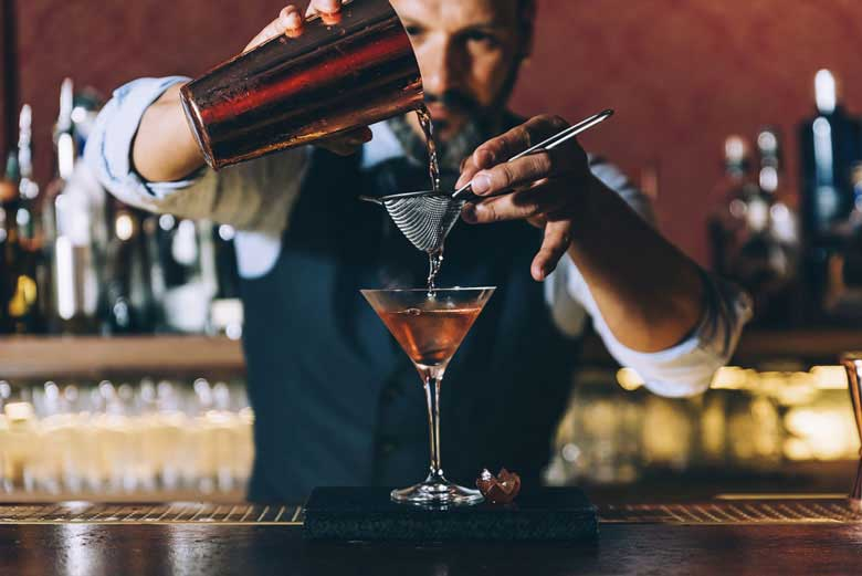 Barman pouring a cocktail